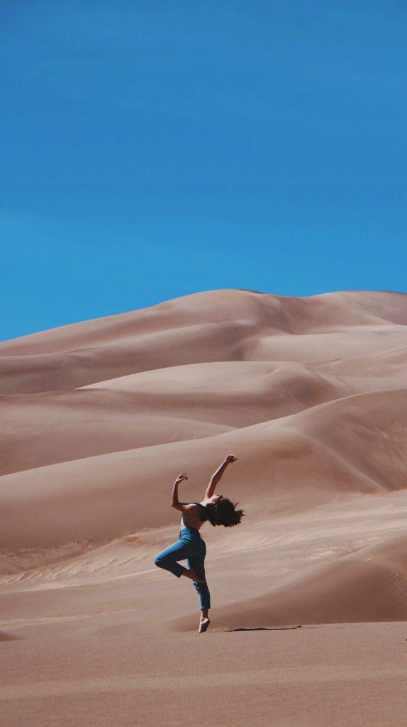 woman dacing on sand